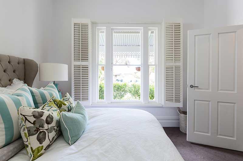 white shutters on window in bedroom